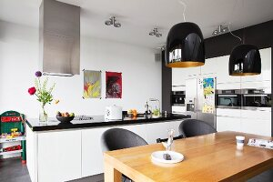 Dining table below black pendant lamps in white, open-plan kitchen with free-standing counter and fitted appliances