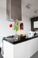 Free-standing counter with black stone counter, white fronts and stainless steel extractor hood