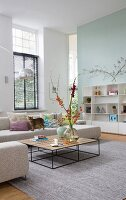 Coffee table with delicate frame and beige corner sofa in spacious, high-ceilinged interior