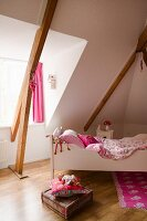 Girl's bedroom with white child's bed in converted attic