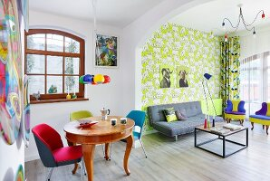 Colourful living area with patterned wallpaper in retro interior with antique dining table