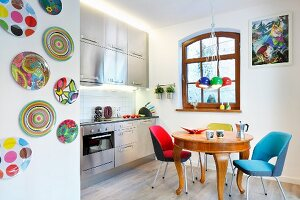 Brightly coloured, retro, upholstered chairs around antique, exotic-wood table, stainless steel kitchen counter and wall plates in open-plan kitchen