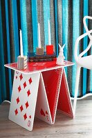 Whimsical side table in red and white with playing card motif, various candlesticks and white rabbit ornament in front of striped curtains