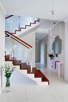 Elegant white hallway with glossy floor tiles and staircase with exotic-wood treads and risers