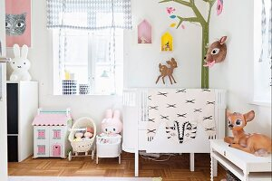 Cot in corner of room with mural of stylised tree and deer ornaments