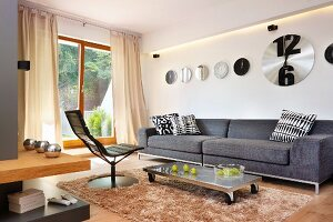 Modern swivel chair and grey couch around coffee table with castors on flokati rug below collection of clocks on wall