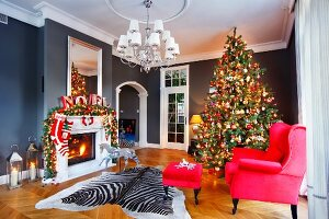 Red armchair and footstool and zebra-skin rug in front of decorated Christmas tree