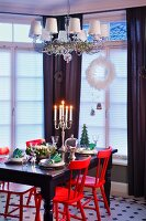 Red-painted chairs at black table below chandelier with small lampshades