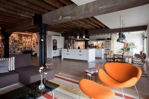 Orange, retro, designer armchair with matching footstool in lounge area in open-plan loft with kitchen and dining areas