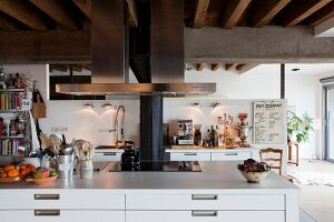 White island counter with drawers and stainless steel extractor hood in loft interior