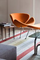 Orange, retro, designer easy chair with matching footstool and side table in fifties style