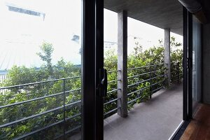 Open, glass sliding door leading to balcony with steel balustrade