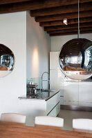 Spherical lamps with chrome and transparent surfaces in front of modern, white kitchen