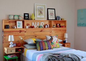 Double bed with colourful scatter cushions and wooden headboard panel with youthful ornaments on integrated shelves and bedside table