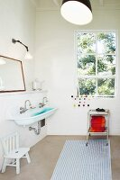 Simple bathroom with white and blue striped rug, trolley below window and trough-style sink to one side