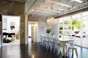 Retro, metal chairs around long, rustic table next to terrace doors; wide, open doorway with view into living room