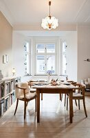 Wooden armchairs around set dining table below retro, pendant lamp in front of bay window
