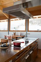 Hob on free-standing counter below extractor hood in modern chalet
