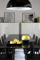 Yellow accents in black dining area; dish of lemons under pendant lamp with black and white lampshade