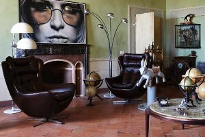 Leather bucket armchair, antique globes and vintage lamps in living room with fireplace