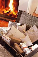 Open suitcase filled with gifts in front of open fire