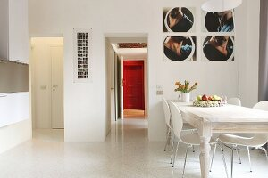 Photographs above dining area with laminated wood chairs and white-painted, country-house table; corridor leading to red front door in foreground