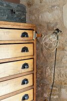Chest of drawers with vintage handles and clip-on lamp against stone wall
