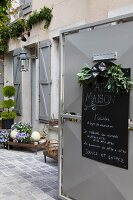 Open courtyard gate with shop opening times on hand-written chalk board and view into charming, rustic courtyard