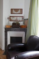 Black leather armchair in front of disused fireplace with ornaments on marble surround below framed, antique lace collars