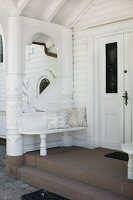 Bench integrated into porch of grand residence with white wooden façade
