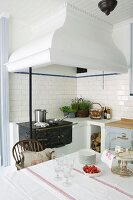Masonry mantel hood above antique cooker in kitchen-dining room