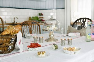 Table set with cheese, bread and tomatoes in Scandinavian, country-house kitchen