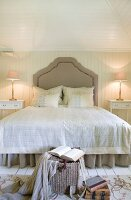 Grand double bed with curved headboard in country-house bedroom with pale wood panelling
