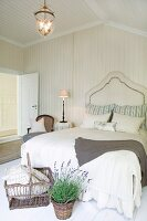 Basket and potted lavender at foot of double bed with elegant headboard