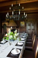 Wrought iron candle chandelier above set dining table and simple, leather-upholstered chairs in old dining room