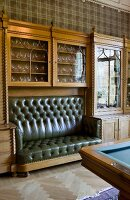 Glass-fronted cabinet with carved, vertical ornamentation and integrated, leather, button-tufted bench; corner of billiard table in foreground