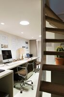 Study with long desk along wall, classic office chair suspended ceiling with recessed lights and staircase to one side
