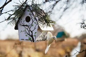 A bird house with a bird figurine and pine tree decoration