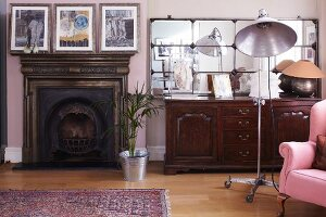 Open fireplace with wooden surround next to antique sideboard with retro studio lamp and armchair to one side