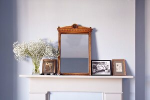 Antique mirror with carved frame amongst photos on mantelpiece against pastel lilac wall
