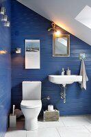 White sink and toilet on blue-painted wooden wall in attic bathroom