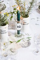 Lit candle in glass and white china vases of herbs on table