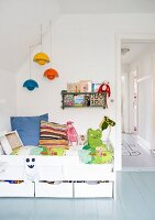 White children's bed with drawers and colourful pendant lamps hanging from the sloping wall