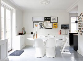 White Panton chairs around an oval table in an open plan dining room with terrorist doors and country house-style charm
