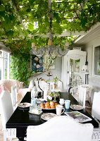 Black-painted table and white chairs on veranda below climber-covered pergola