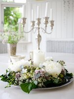 Wreath of flowers around white pillar candle on silver tray in front of silver candelabra