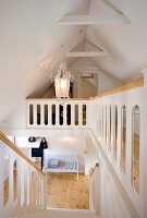 Staircase and landing in renovated attic; white-painted wooden staircase and wooden handrail