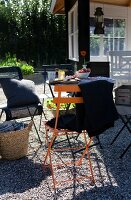 Blanket and cushions on colourful folding chairs on gravel terrace in garden