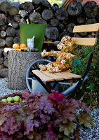 Teddy bear from patterned fabric on wooden folding chair next to tree trunk table in garden