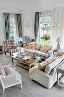 Pale, country-house-style sofas and armchairs in elegant interior with grey patterned wallpaper